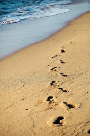 Voetafdrukken op zand strand