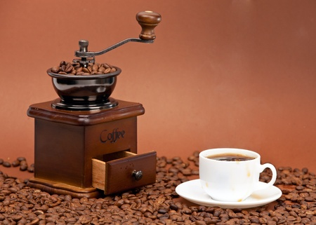 Coffee grinder and cup of coffee photo