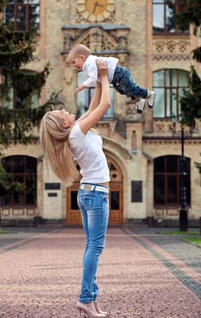 Happy young woman lifting her son high up photo