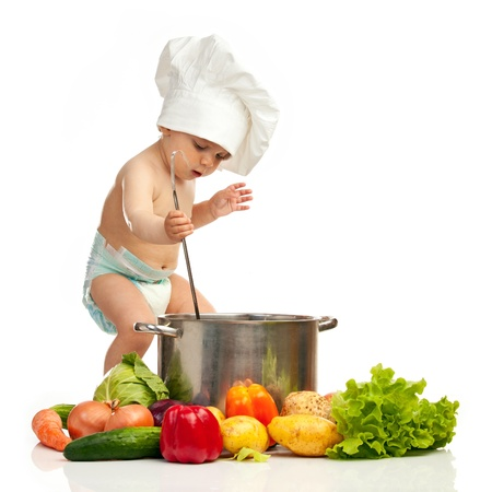 Little boy with ladle, casserole, and vegetables photo