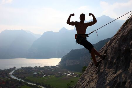 Silhouette of a rock climber flexing biceps photo