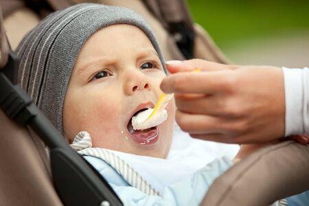 Mom feeding one-year old boy sitting in stroller photo