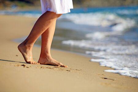 piedi nudi di bambine: Immagine ritagliata di una giovane donna camminare su una spiaggia Archivio Fotografico