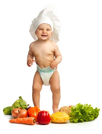 Little boy in chef s hat among fresh vegetables photo