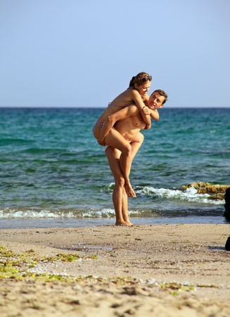 man carrying woman: Young caucasian couple at the beach