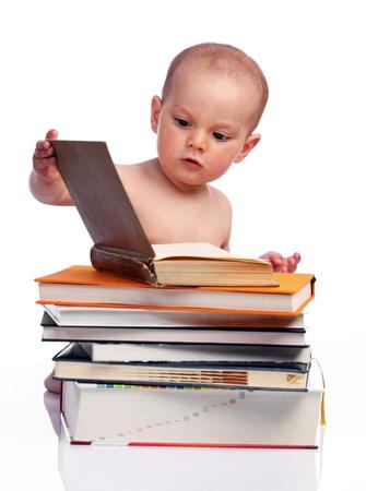 Kleine jongen zittend achter een stapel boeken