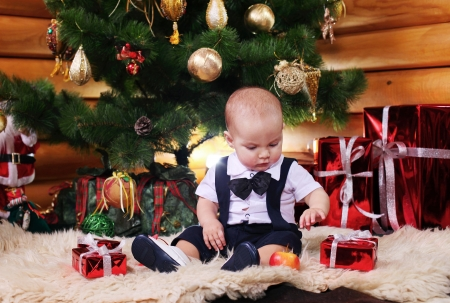 Cute baby boy with Christmas gifts photo