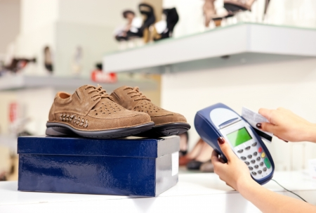 Moment of payment using credit card terminal in shoe store  Selective focus on pair of male shoes on top of box   photo