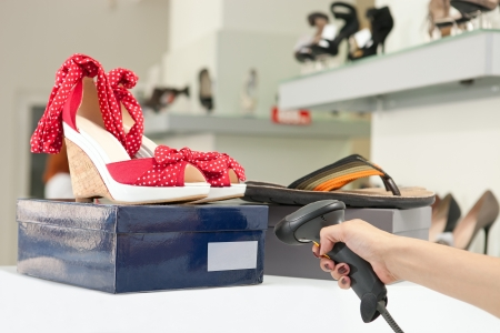 Cropped view of shop assistant scanning code on shoe box  Image with selective focus   Stock Photo - 16626965