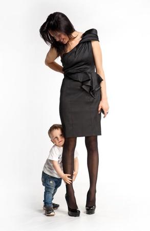 let on: El ni�o peque�o se aferra a la pierna de la madre s no quieren dejarla ir Foto de archivo