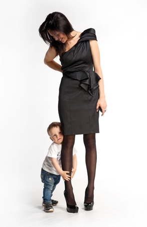 Little boy clinging to mother s leg unwilling let her go  photo