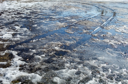 snow field: Spring slush  Ground covered with thawing snow and car trace  Blue sky reflected in water   Stock Photo