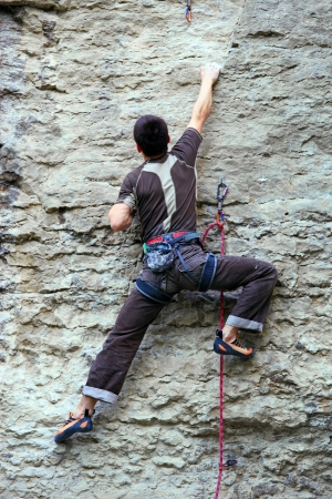 climbing sport: Rock climber climbing up a cliff