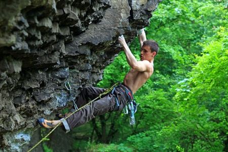 Rock climber preparing to the next movement, with bright green  Stock Photo - 16953843