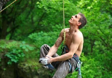 Tired rock climber hanging on the rope and looking up after falling off from the route  photo