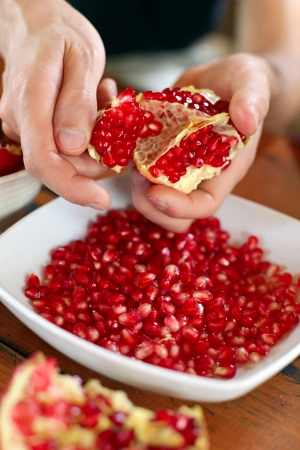 pomegranate juice: Male hands peeling pomegranate fruit, image with selective focus