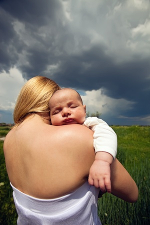 Baby sleeping on mother s shoulder against rural background Stock Photo - 16954006