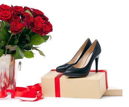 rosas negras: Pares de zapatos femeninos y ramo de rosas sobre fondo blanco Foto de archivo