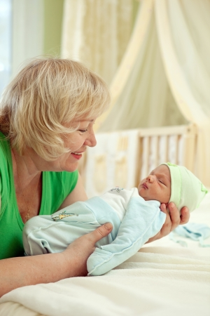 grandmother and grandson: Happy mature woman holding her newborn grandson