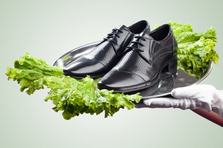 Waiter s hands holding tray with pair of male shoes decorated with lettuce  Concept of fresh product immediately delivered to customer  With clipping path   photo