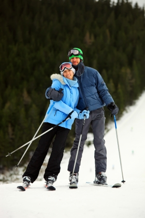 Portrait of cheerful young couple on skis against conifers background  photo