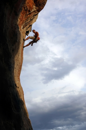 climbing mountain: Silhouette of rock climber against cloudy sky background  Stock Photo