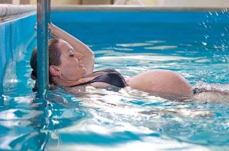 big breast: Young pregnant woman in swimming pool  Stock Photo
