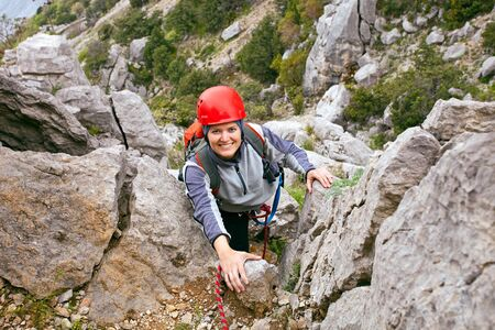Portrait of cheerful female climber ascending a rock Stock Photo - 16627124