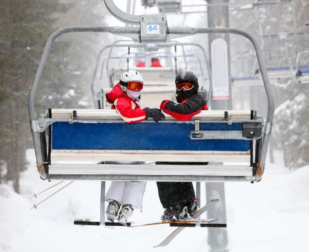 lift and carry: Skiers on a ski-lift  Stock Photo