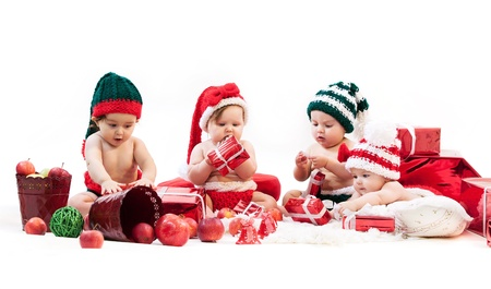 christmas baby: Four babies in xmas costumes playing among gifts