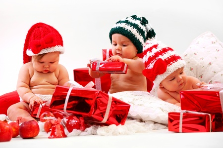Three babies in xmas costumes playing with gifts  Stock Photo - 16698551