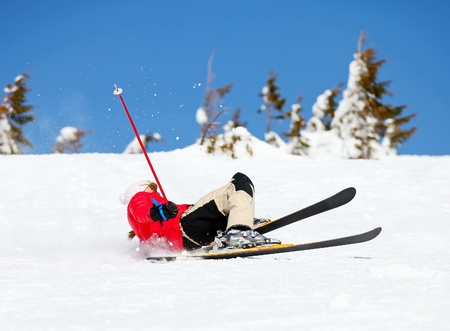 injured woman: Girl skier falling down white on mountain slope  Stock Photo
