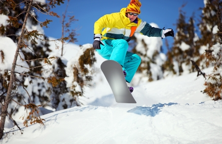Snowboarder jumping on mountain slope  photo