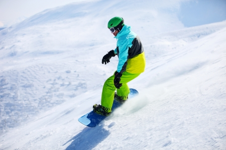 snowboard: Snowboarder sliding down a slope on a sunny day
