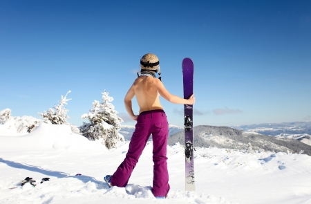 nude outdoors: Rear view of female skier standing topless on mountain slope