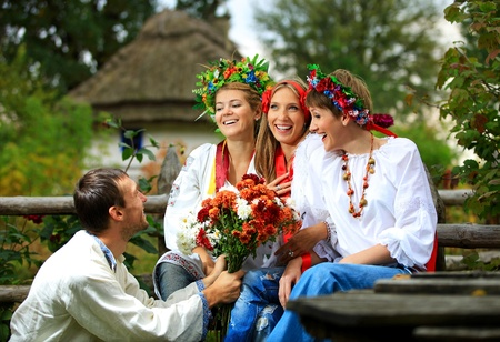 Young people in dressed in Ukrainian shirts flirting  The guy giving flowers to the girl he loves   photo