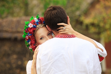 tenderly: Young couple in Ukrainian national costumes hugging tenderly outdoors  Stock Photo