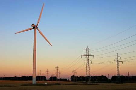 Electricity pylons and wind turbines against sky at sunset Stock Photo - 17759144