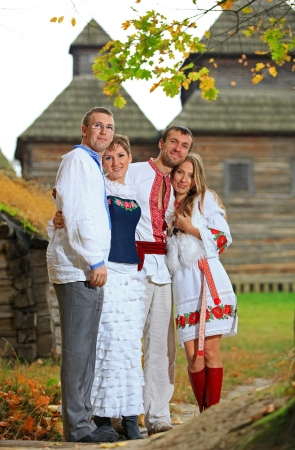 Two young couples in Ukrainian style clothing posing outdoors  photo