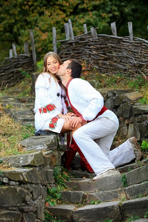 Young romantic couple in Ukrainian style clothes outdoors  photo