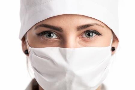doctor mask: Closeup of a young female doctor wearing a mask and a hat over white  Stock Photo