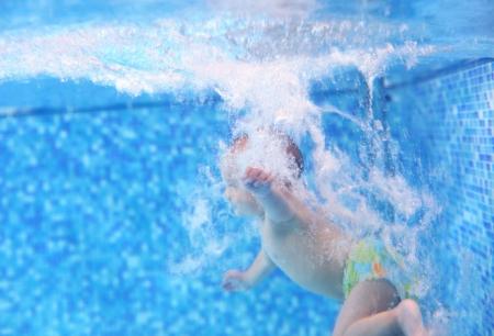 Kleine jongen na het duiken in een zwembad, met de hand en water bubbels in focus