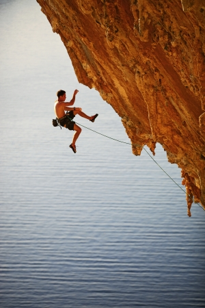 Rock climber falling of a cliff while lead climbing  photo