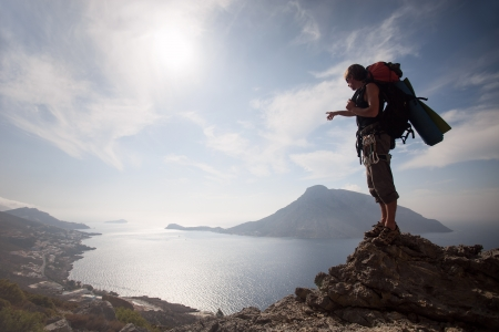 mountaineering: Young man standing on a rock against picturesque view of sea