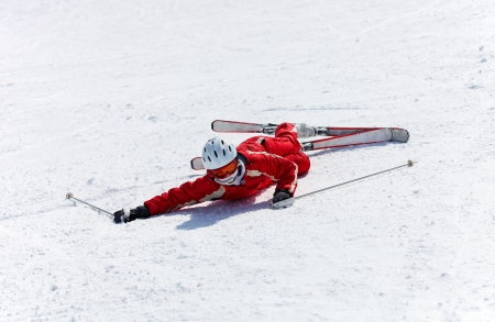 sun down: Female skier after falling down on a mountain slope  Stock Photo