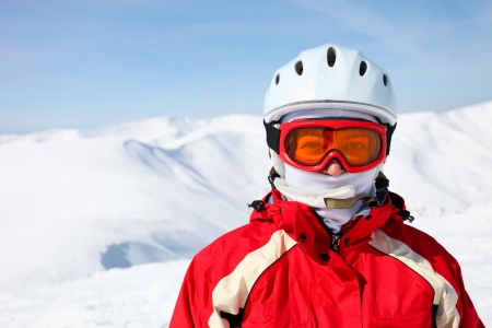 ski mask: Closeup portrait of a female skier standing on a skiing slope