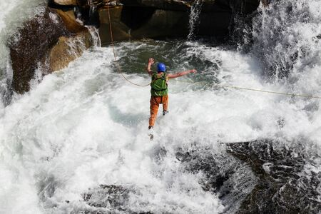 lifejacket: Young man rope jumping in rapid waters of a mountainous river