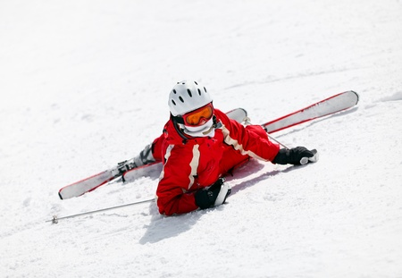 sun down: Female skier looking at the camera after falling down on mountain slope