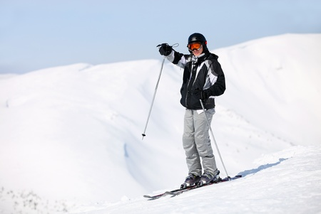 Young male skier pointing at something while standing on top of mountain  photo