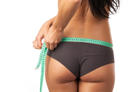 bikini bottom: Cropped view of a beautiful young woman measuring her body over white background  Stock Photo